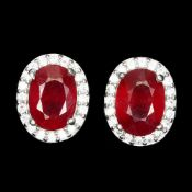 A pair of 925 silver stud earrings set with oval cut rubies surrounded by white stones, L. 0.9cm.