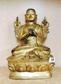 A Tibetan gilt bronze figure of a seated Buddhist Deity, H. 33cm.
