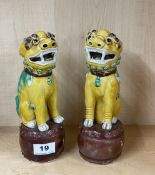 A pair of Chinese glazed porcelain lion dog figures standing on drums, H. 23cm. Condition: one A/F.