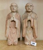 A pair of Chinese carved wood and painted figures of monks, H. 30cm.
