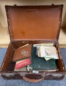 A small vintage suitcase of photograph albums and other items.