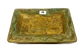 An early 20th Century Chinese gilt bronze bowl standing on four raised feet depicting cranes in a