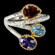 A 925 silver ring set with garnet, tanzanite and blue topaz.