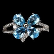 A 925 silver flower shaped ring set with pear cut blue topaz and white stones.