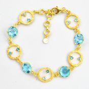 A 925 silver gilt bracelet set with faceted blue topaz, L. 21cm.