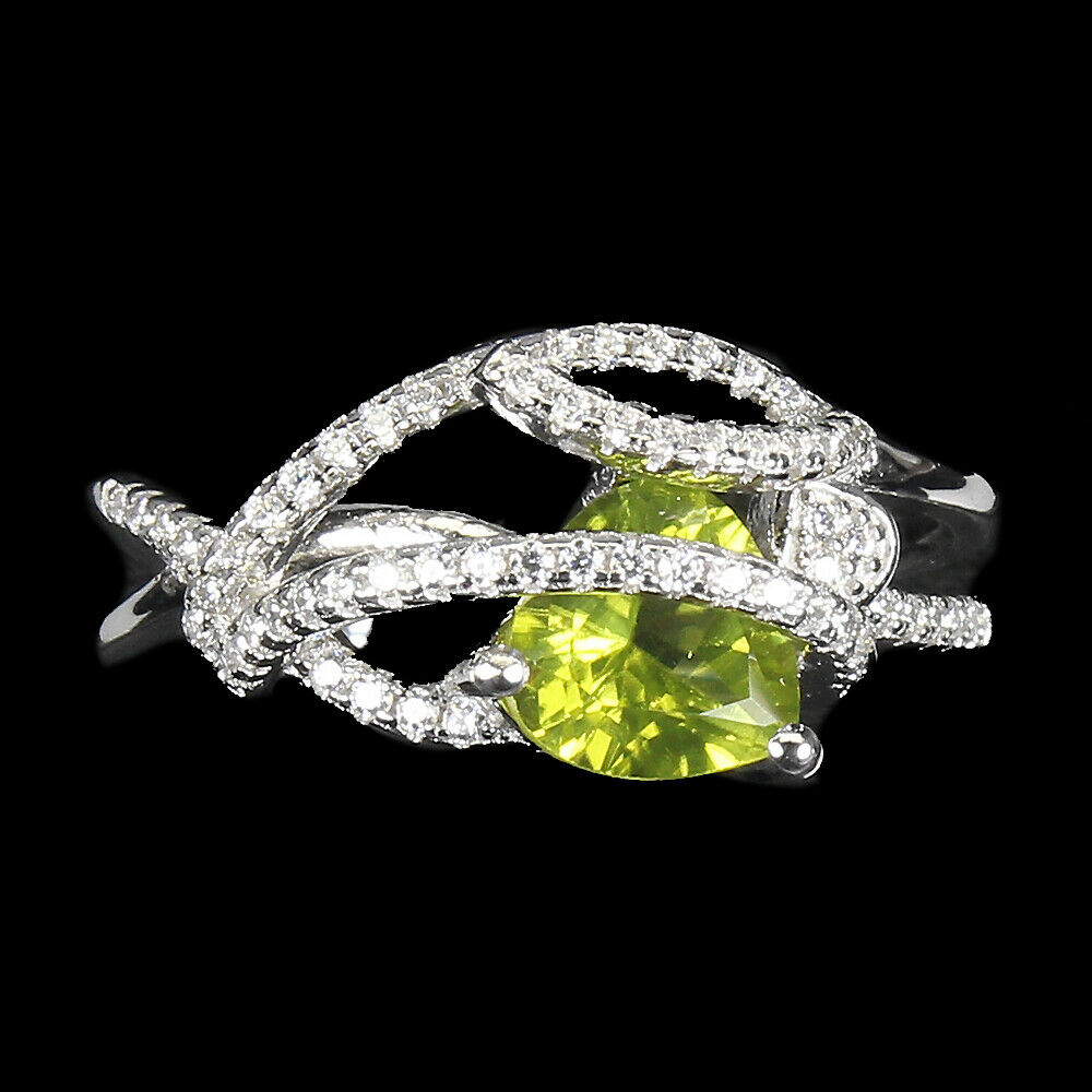 A 925 siver ring set with a trillion cut peridot and white stones, (R).