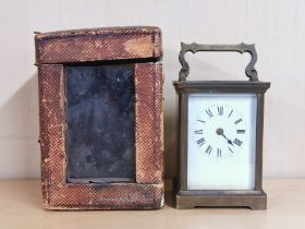 An antique brass carriage clock with carrying case, H. 14cm.