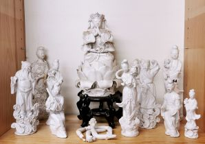 A group of Chinese Blanc de Chine porcelain figures including a deity with loose arms.