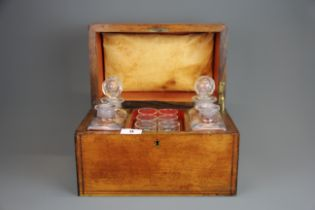 A 19th Century walnut veneered tantalus case with four decanters and six glasses. Case size, 30.5