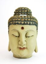 A carved wood and painted Buddha head H. 30cm