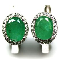 A pair of 925 silver cluster earrings set with oval cut emeralds surrounded by white stones, L. 1.
