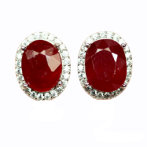 A pair of 925 silver earrings set with an oval cut ruby surrounded by white stones, L. 1.5cm.