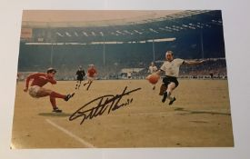 Geoff Hurst signed 12 x 8 inch colour photo scoring in 1966 football World Cup Final. Good