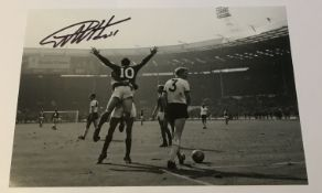 Geoff Hurst signed 12 x 8 inch b/w photo celebrating scoring in 1966 football World Cup Final.