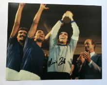 Dino Zoff signed 10 x 8 inch colour photo with World Cup Football trophy held aloft. Good condition.