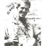 Sir Ed Hillary signed 12 x 8 inch b/w photo smiling shot with mug of tea in hand. Good condition.