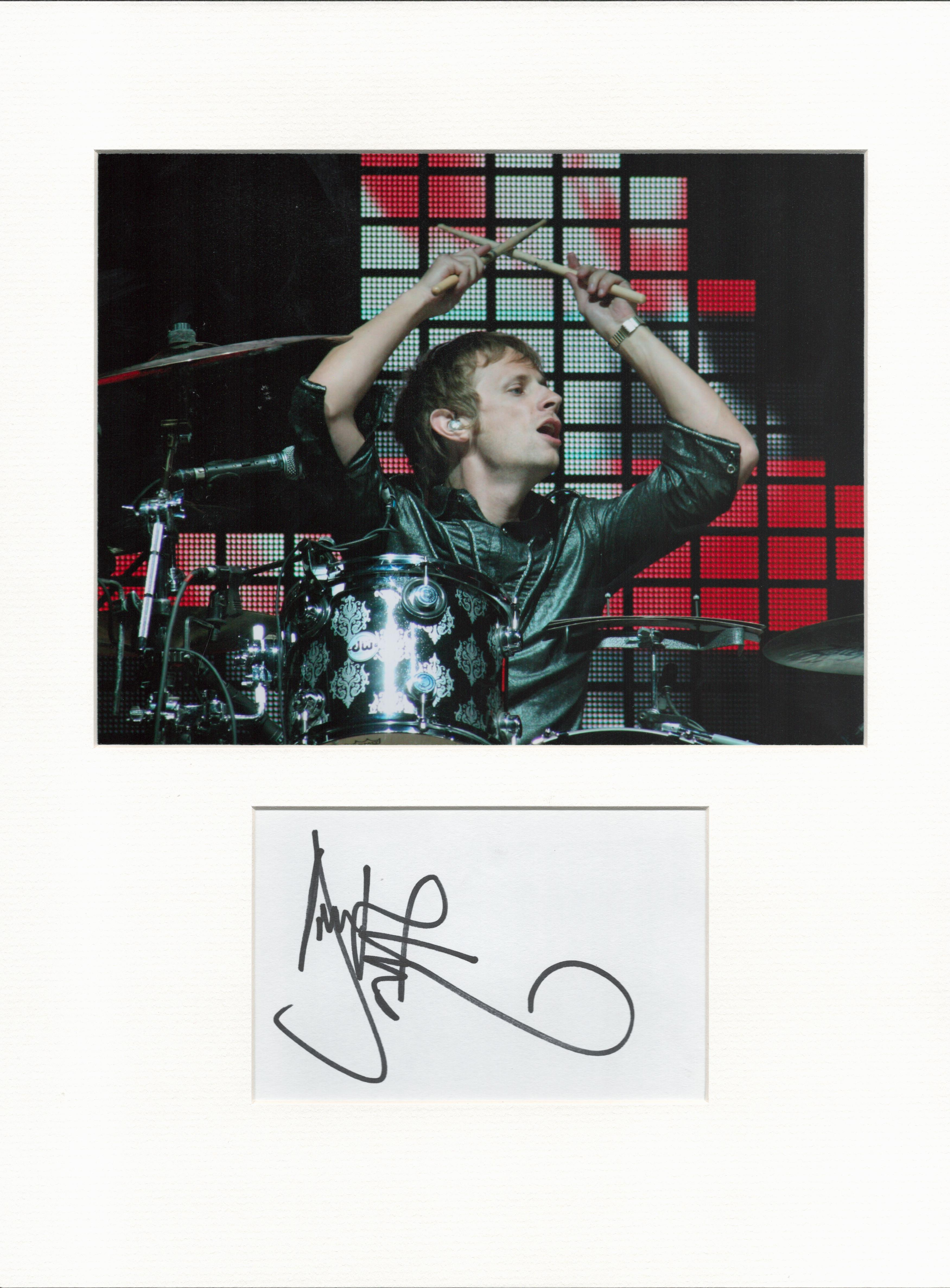 Dominic Howard (Muse) signature piece in autograph presentation. Mounted with photograph to