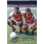 Autographed ARSENAL 12 x 8 photo - Col, depicting Arsenal's VIV ANDERSON and KENNY SANSOM striking a