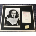 Bette Davis signed Christmas card, with a personal dedication, mounted with a black and white 10x8