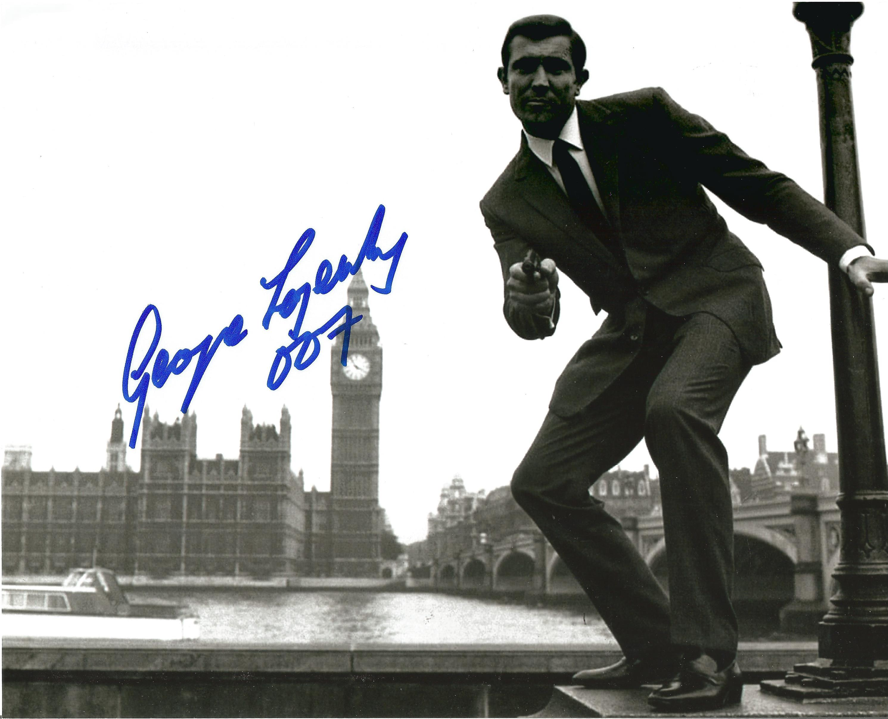 James Bond George Lazenby signed 10 x 8 inch b/w photo gum in hand with Houses of Parliament in
