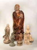 A Chinese lacquered wood figure of a standing lohan, on lotus base, 62.5; and four other lohan /
