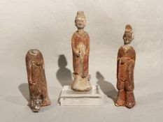 Three Chinese painted pottery standing figures, perhaps Han Dynasty, of a lady and two men,