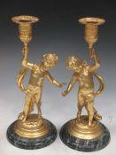 A pair of gilt metal cherub candle sticks, late 20th century, 25cm high