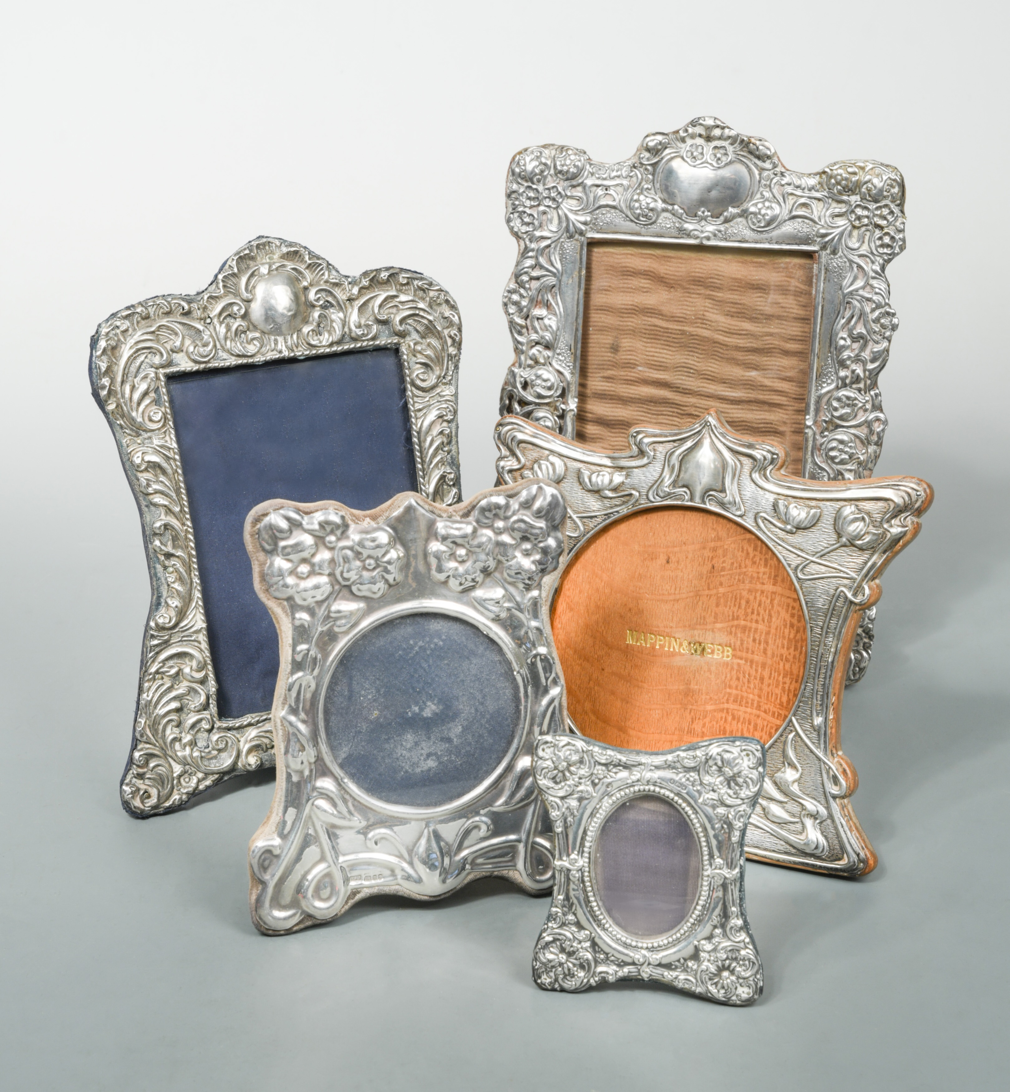 Four early 20th century silver easel back photograph frames together with a later example,