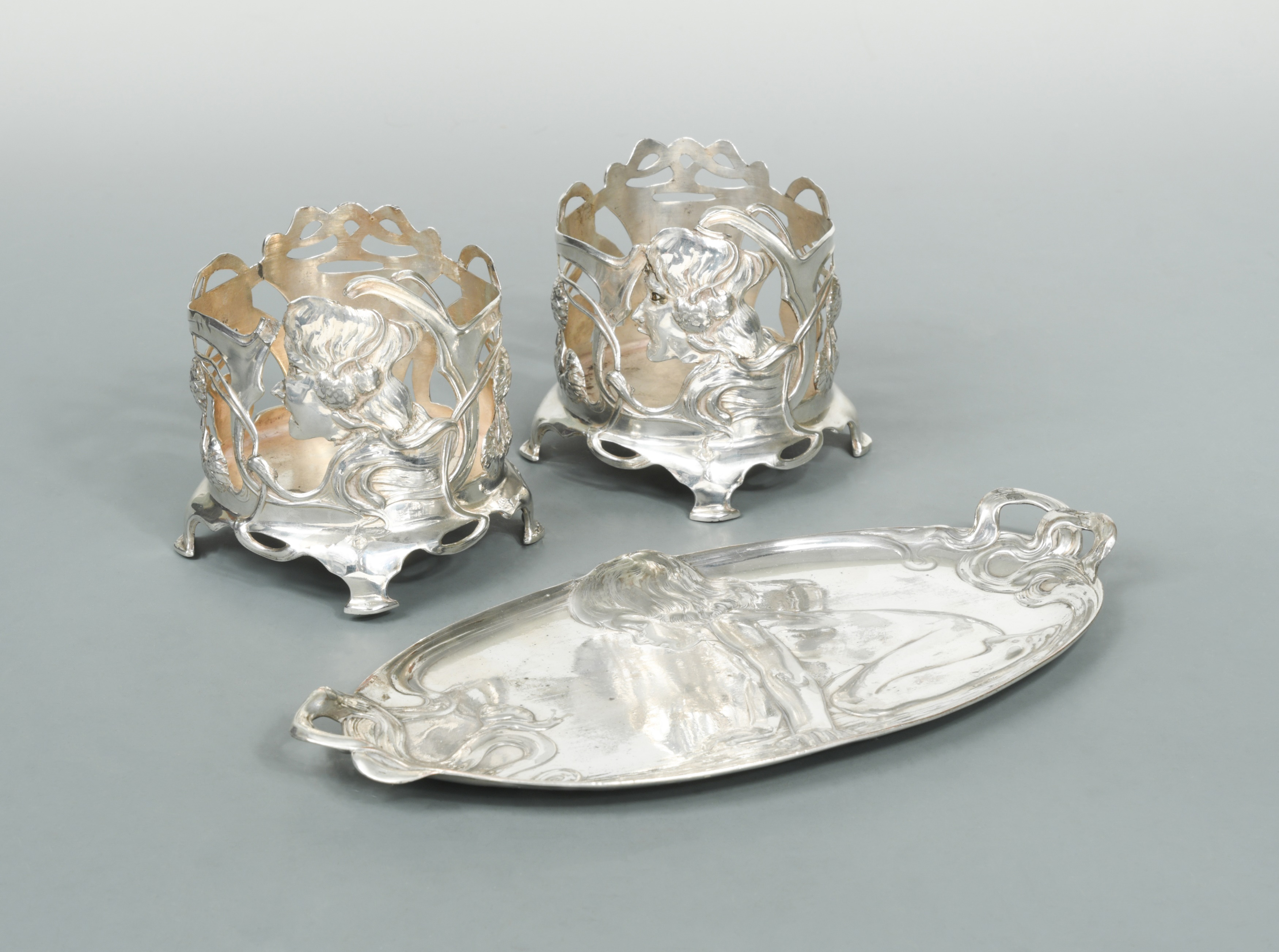 A German metalwares dressing table tray and a pair of bottle coasters all in the Art Nouveau style,