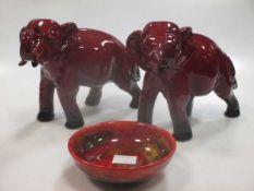 Two Royal Doulton flambe elephants, signed 'FM' (Fred Moore) and a small Royal Doulton flambe saucer