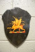 An early 20th century painted armorial shield of a Griffin, 34cm high, together with seven various