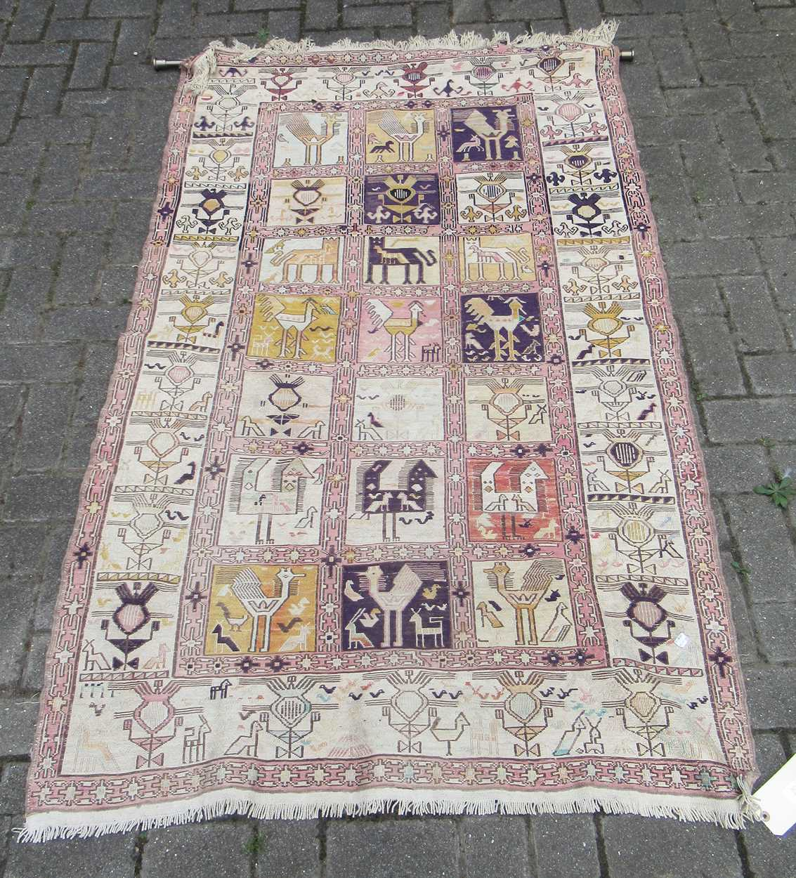 A tribal pale ground rug with bands of animals in squares and repeating border pattern, now