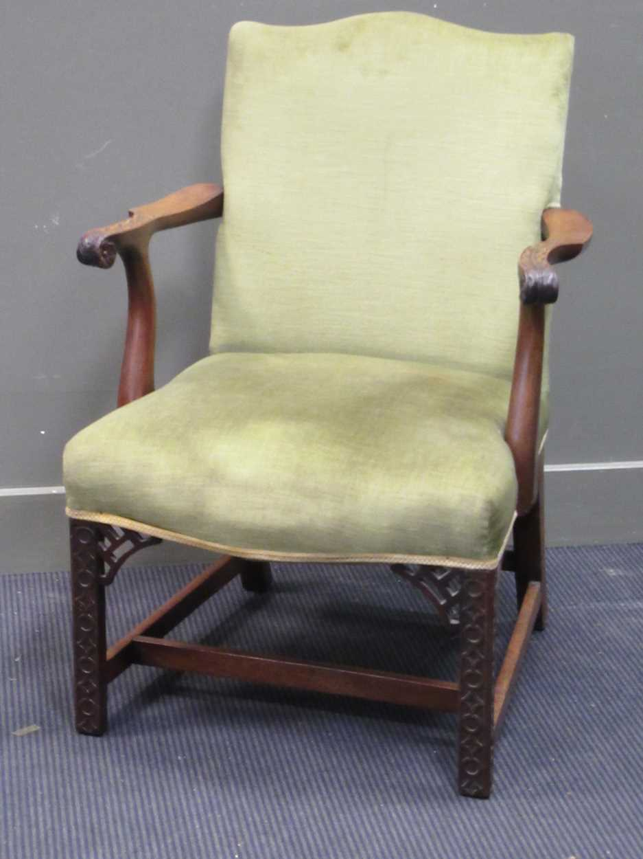 A George III style elbow chair with serpentine back and seat on carved legs with fret carved