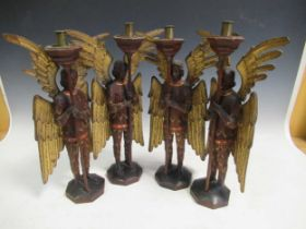 A set of four carved and gilt candlesticks modelled as angels, 40cm high (4)