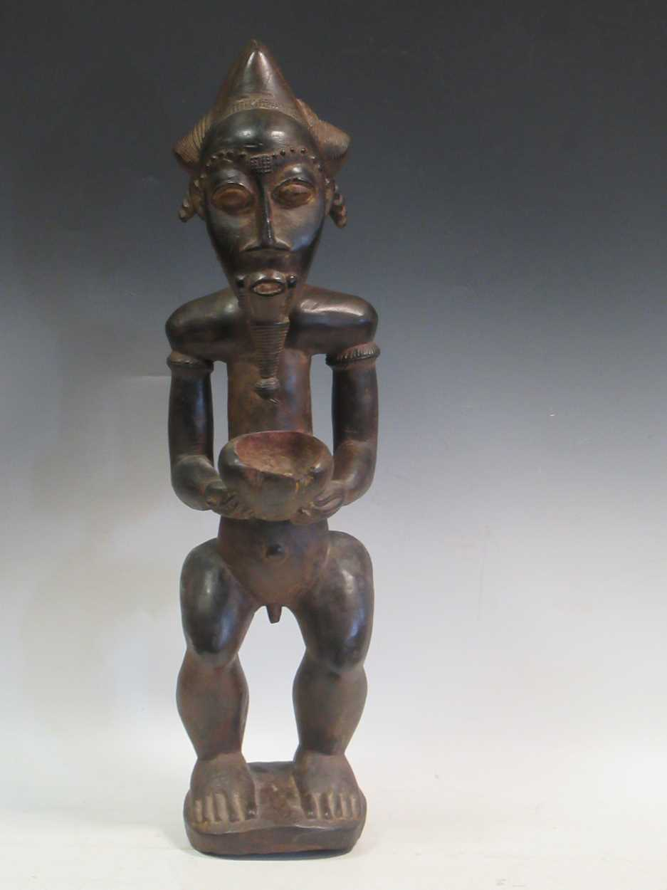 A carved tribal figure of a man, 53cm high