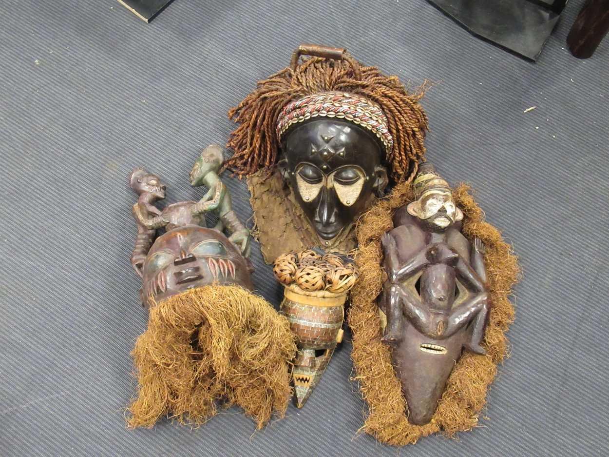 A Chokwe mask, a Yoruba Gelede mask, a Salampasu mask decorated with copper sheets and a Yaka type