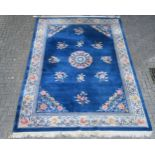 A Chinese wool carpet, with floral sprigs, on a blue ground with ivory border, approx. 375cm long,