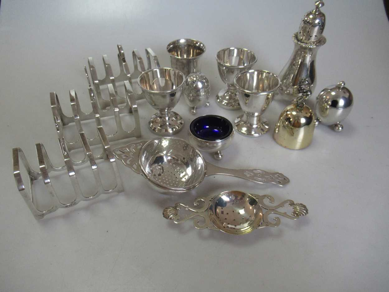 A collection of silverware including 3 toastracks, 4 egg cups, 2 tea strainers, a pepper caster, a
