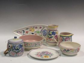 Items of Poole pottery to include a biscuit barrel, two jugs, two bowls, a plate and a leaf shaped