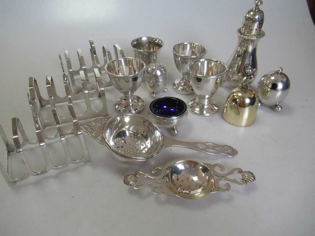 A collection of silverware including 3 toastracks, 4 egg cups, 2 tea strainers, a pepper caster, a - Image 6 of 6