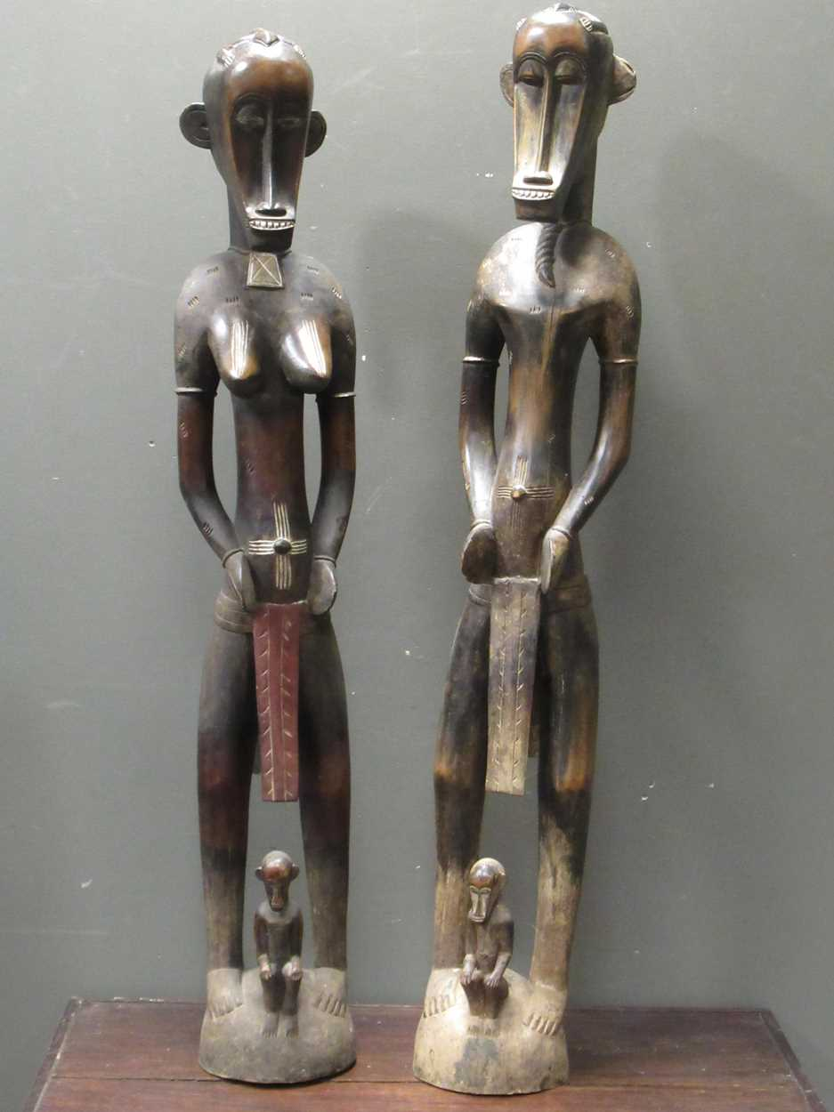 A pair of Senufo style rhythm pounders, comprising of a male (132cm high) and female (129cm high)