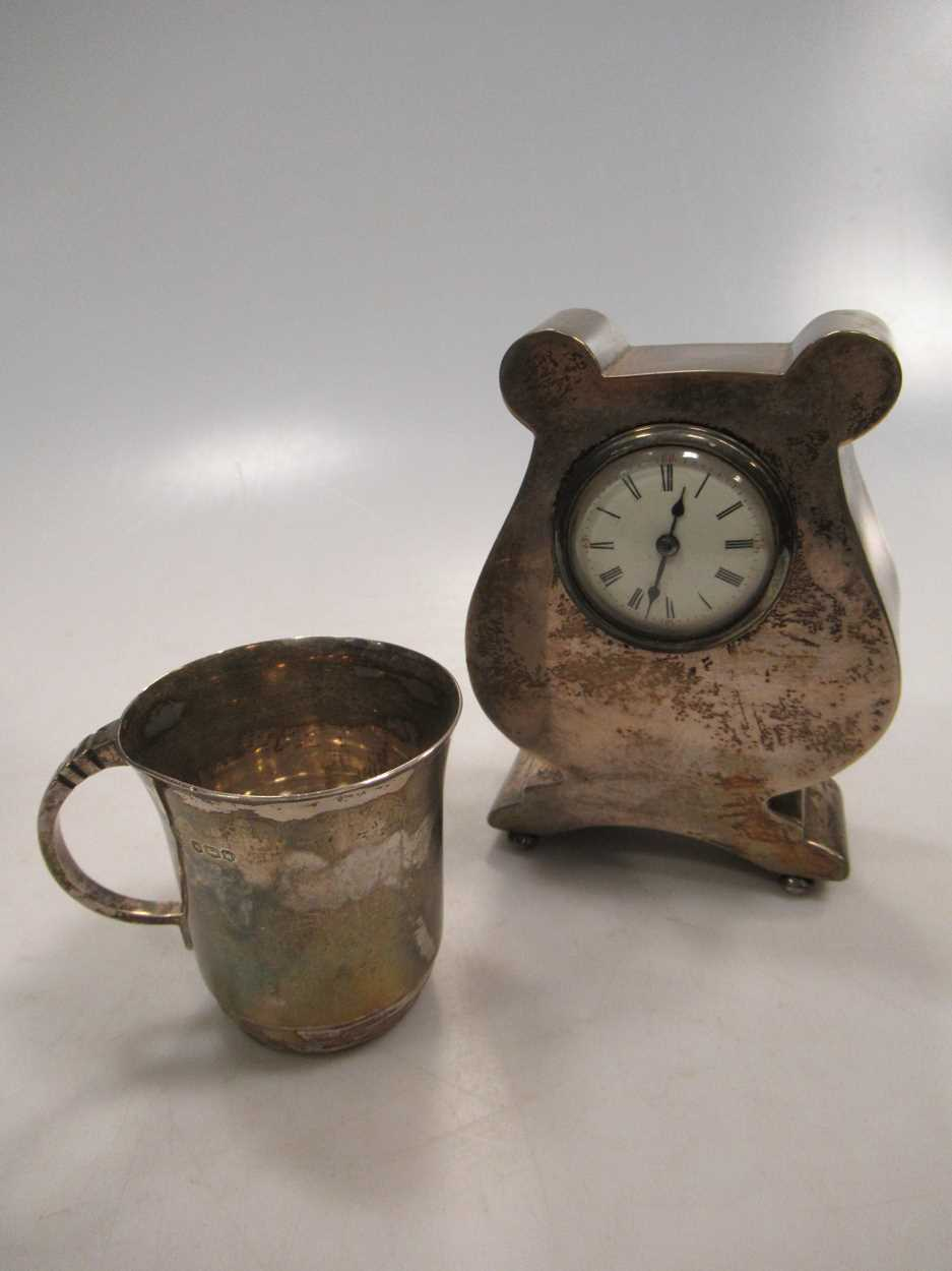 A silver lyre shaped mantle clock, 13cm high and a silver christening mug (2)