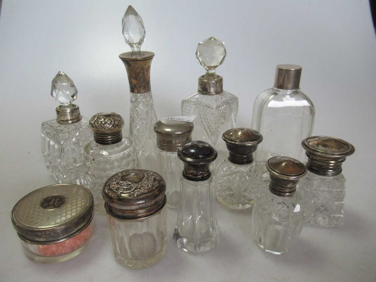 A collection of glass scent bottles some silver mounted