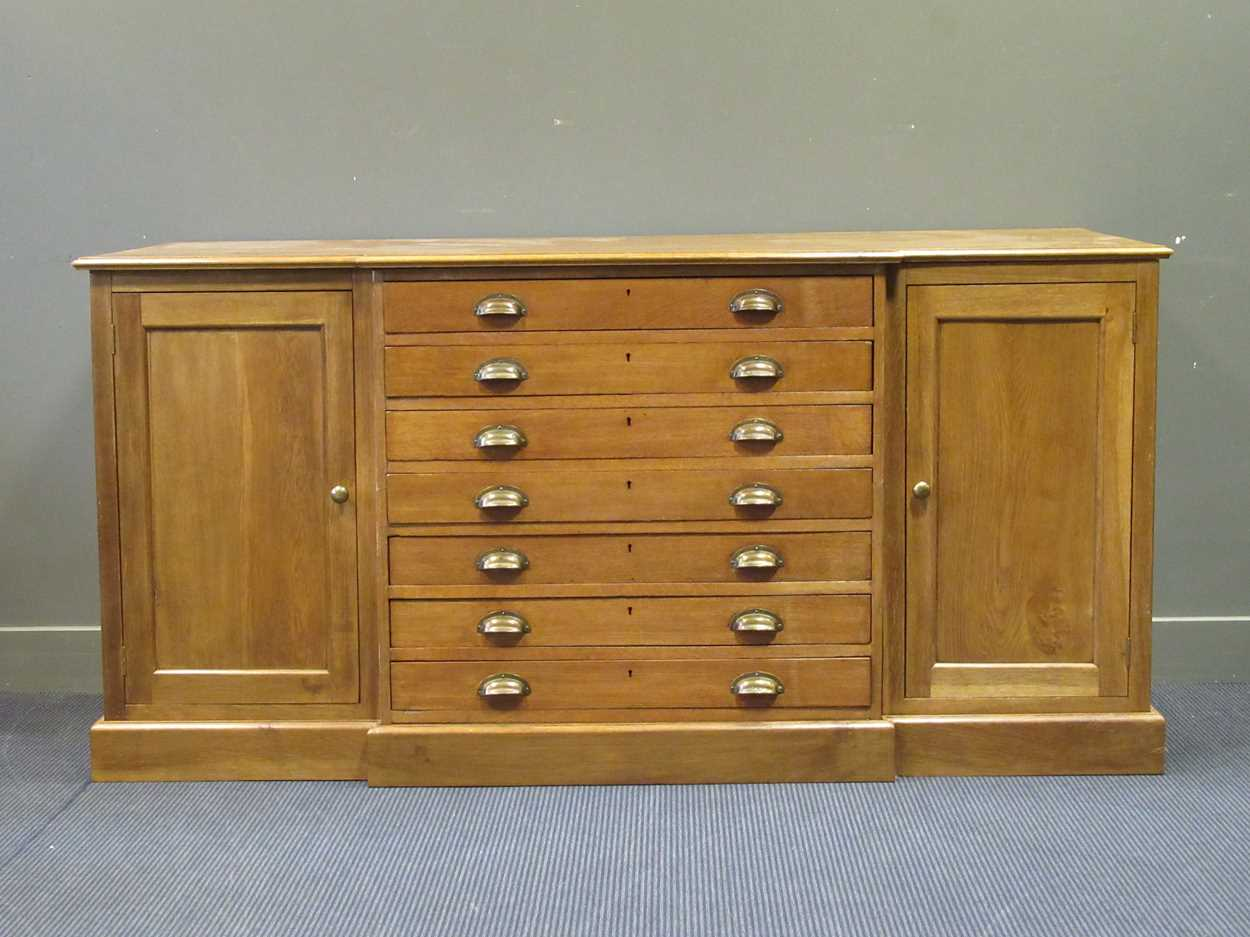 A 20th century blonde oak breakfront plan/ map chest, comprising of seven long drawers flanked by