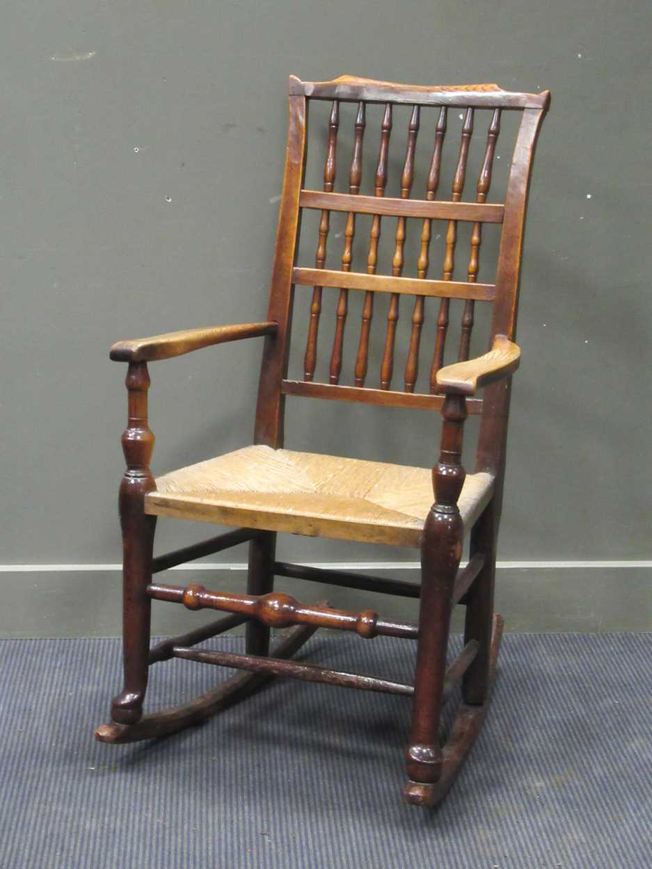 A rush seated stick back rocking chair 108cm high