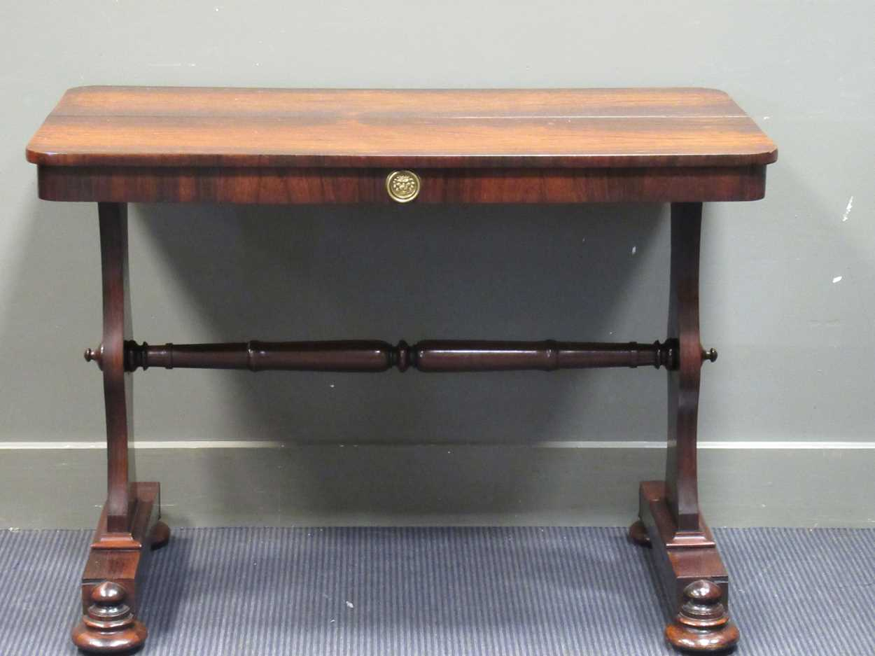 A circa 1830 rosewood library table with single frieze drawer on bun feet and brass castors, 72 x