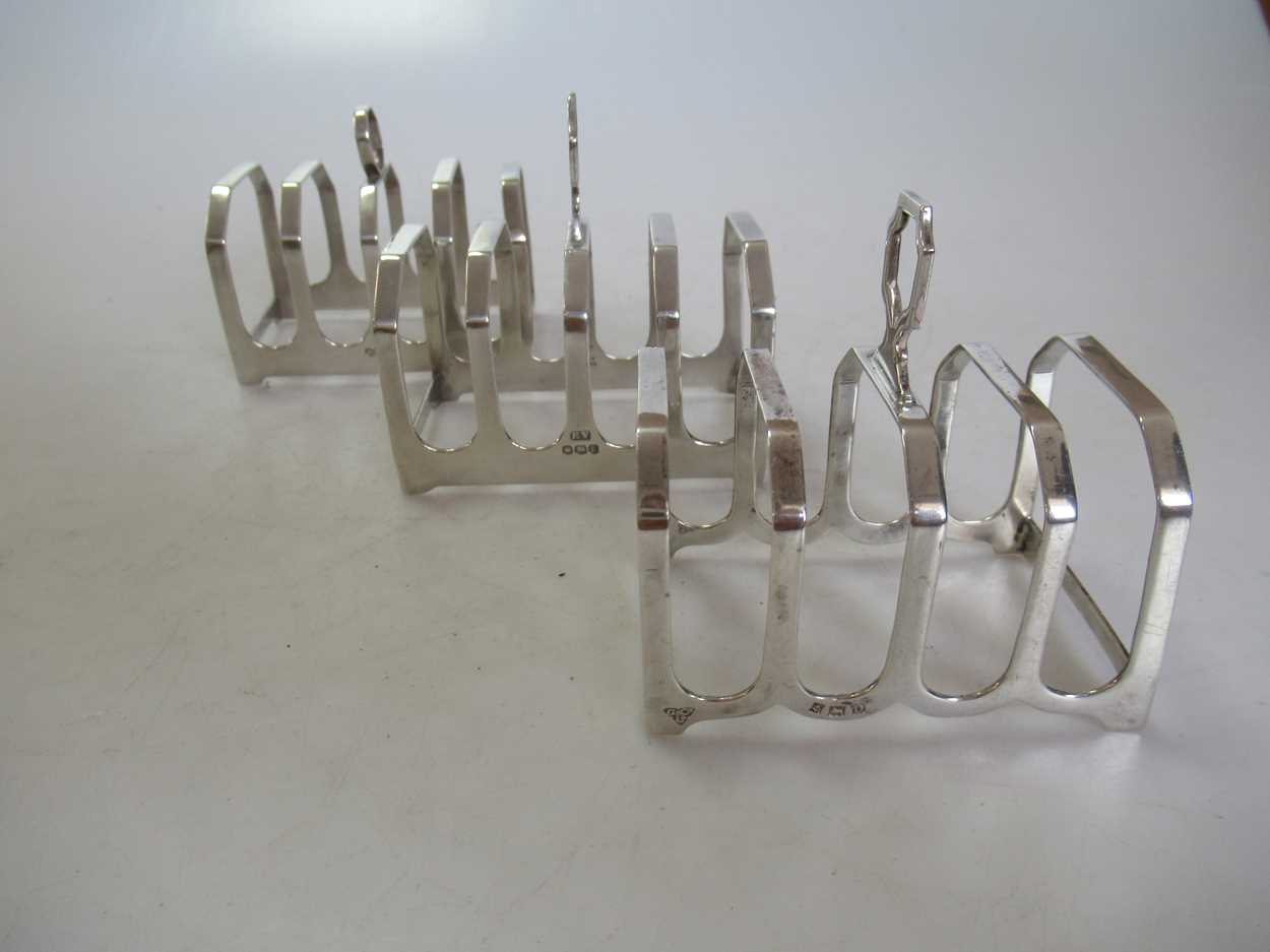 A collection of silverware including 3 toastracks, 4 egg cups, 2 tea strainers, a pepper caster, a - Image 3 of 6