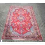 A red ground carpet with central medallian and floral decoration 384 x 242cm