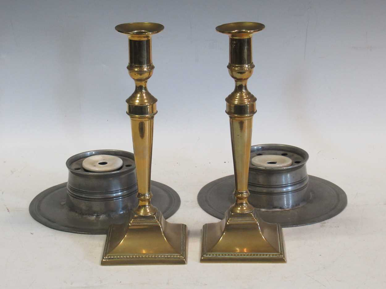 A pair of 18th century peweter inkwells and a pair of George III brass candlesticks