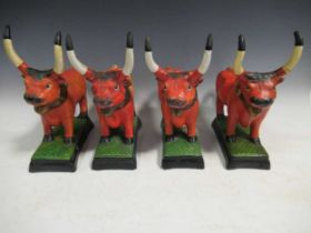 A set of pottery bulls, painted in orange on rectangular bases, 28cm high (4)
